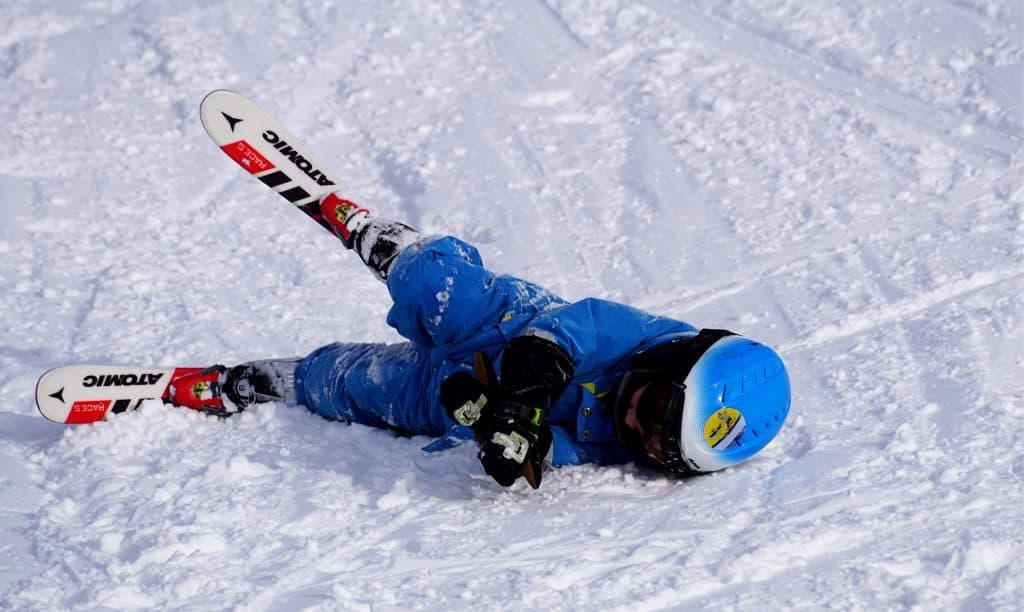 A young child learning to ski and falling